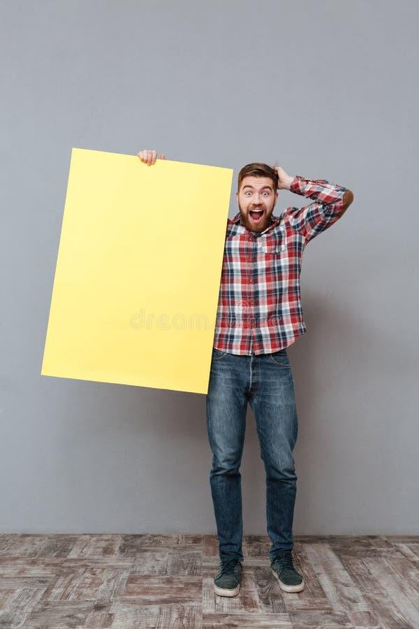 拿着空白的委员会的Surprised人的全长图象 库存照片