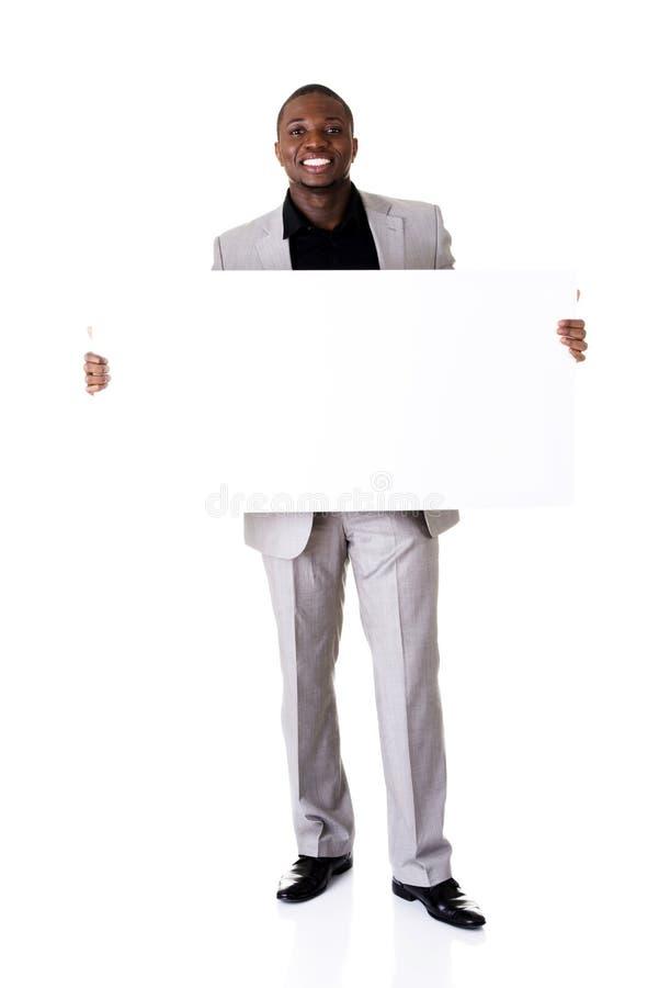 拿着空白的广告的愉快的成功的商人。 免版税库存照片