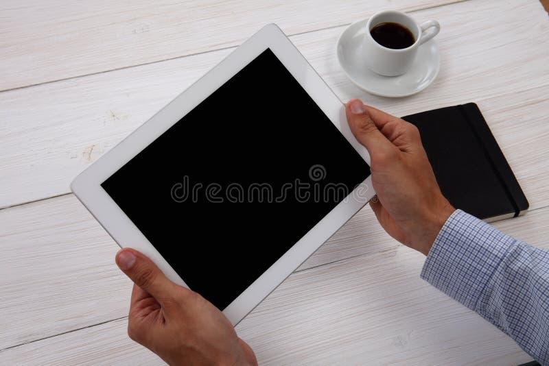 拿着空白的数字式片剂、笔记薄和咖啡的手 库存图片