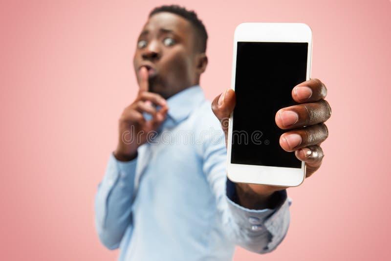 拿着空白的智能手机的可爱的年轻黑人室内画象  免版税库存图片