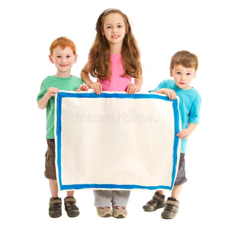 拿着空白的标志的愉快的孩子 免版税库存图片