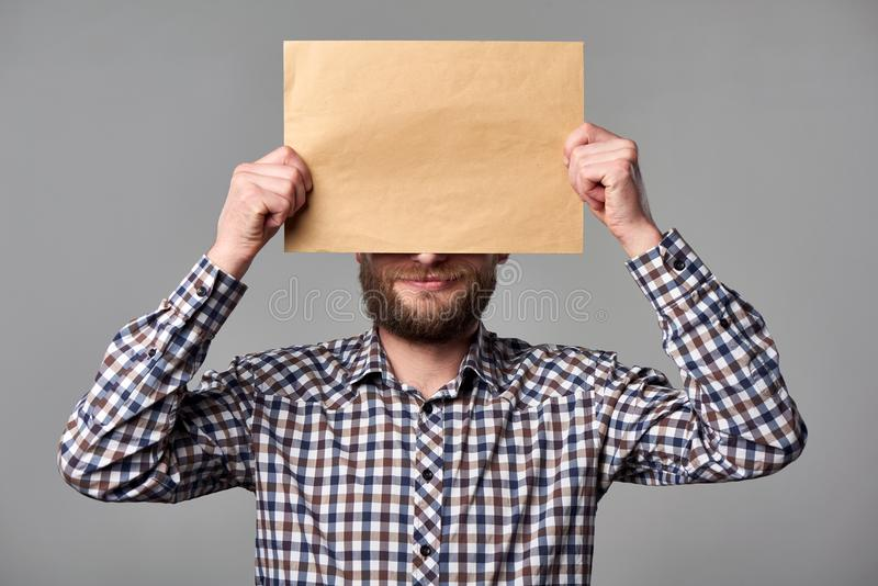 拿着空白的棕色信封的有胡子的人 库存照片