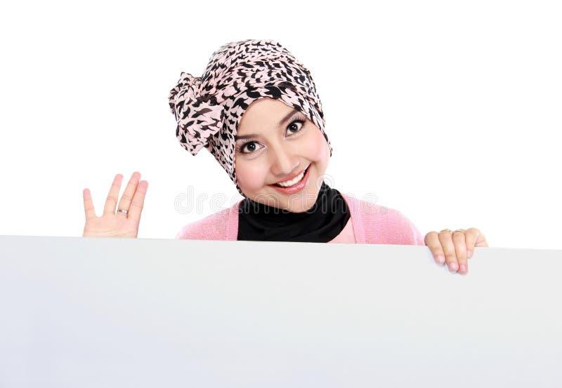 拿着空白的白板的微笑的可爱的回教妇女 免版税库存图片
