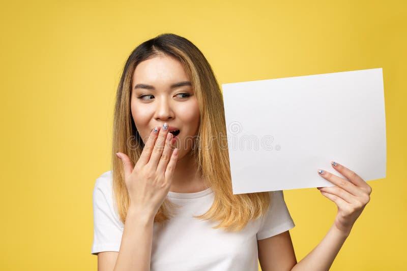 拿着空白的白皮书的可爱的年轻美丽的亚裔学生妇女 库存照片