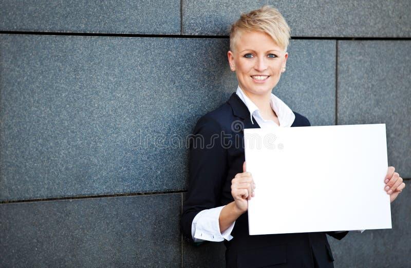 拿着空白的白色标志的女实业家 库存图片