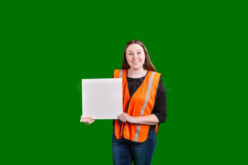 拿着空白的白色标志的年轻女性佩带的橙色反射器背心 免版税库存图片