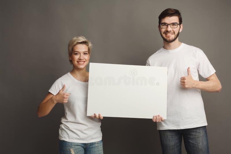 拿着空白的白色横幅的年轻夫妇 免版税图库摄影