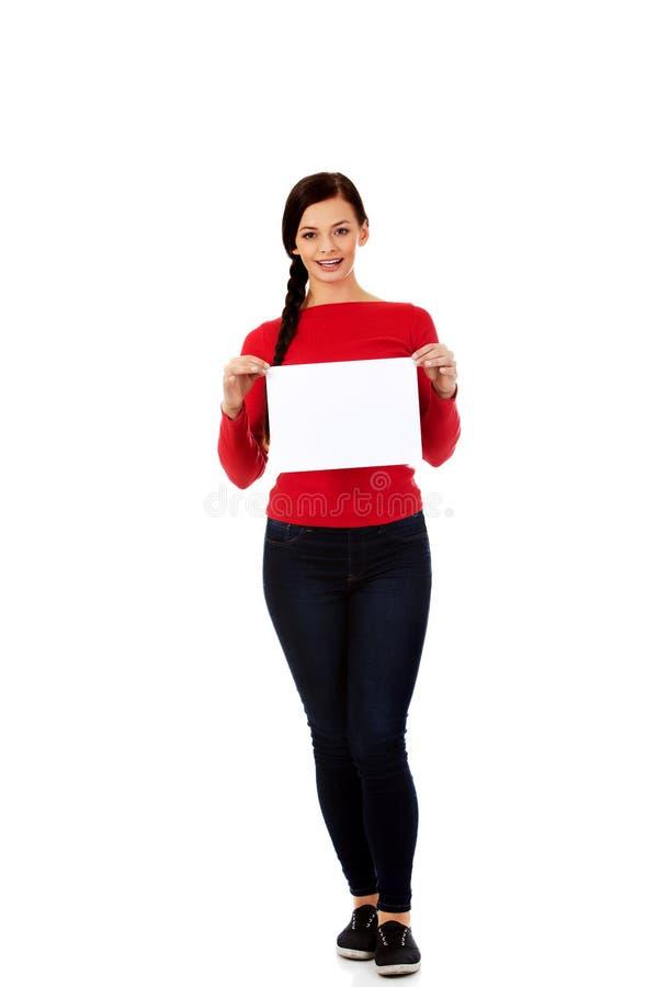 拿着空白的白色横幅的微笑少妇 免版税库存照片