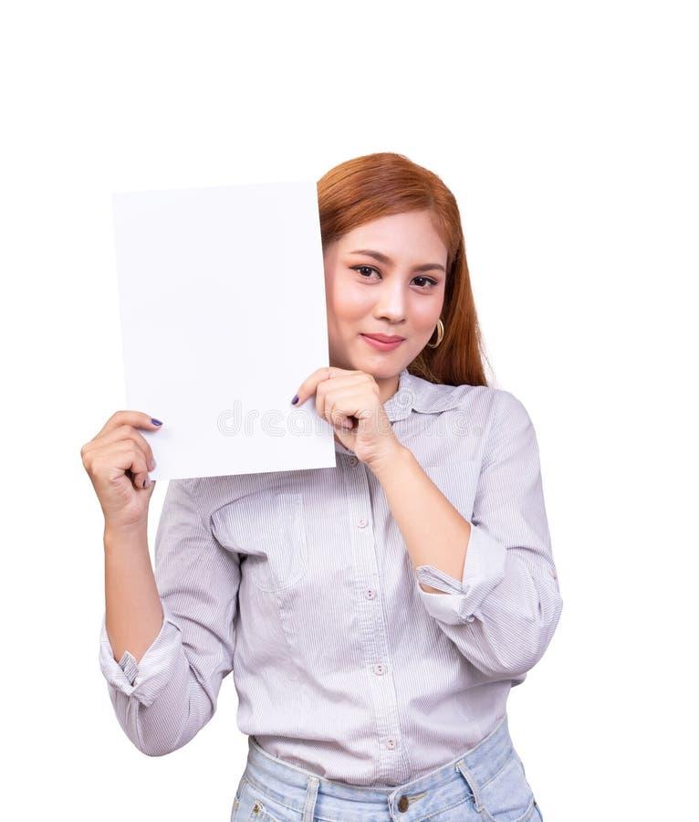 拿着空白的白色横幅,企业标志有裁减路线的厚纸的微笑的亚裔妇女 美丽的女性演播室画象  免版税库存图片