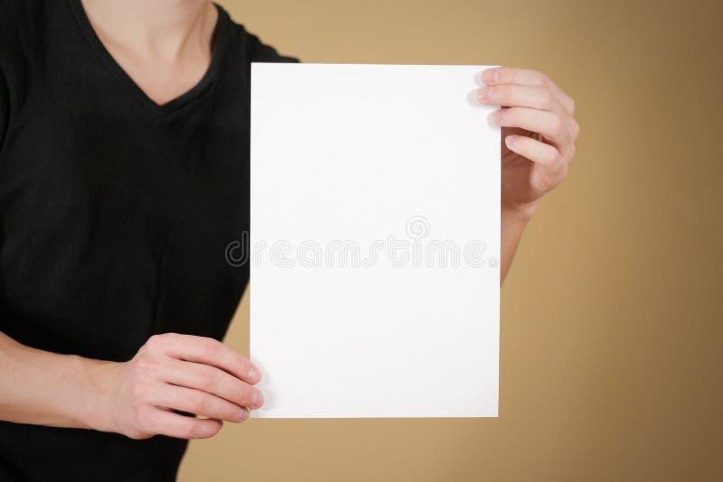 拿着空白的白色A4纸的黑T恤杉的人 prese的传单 免版税图库摄影