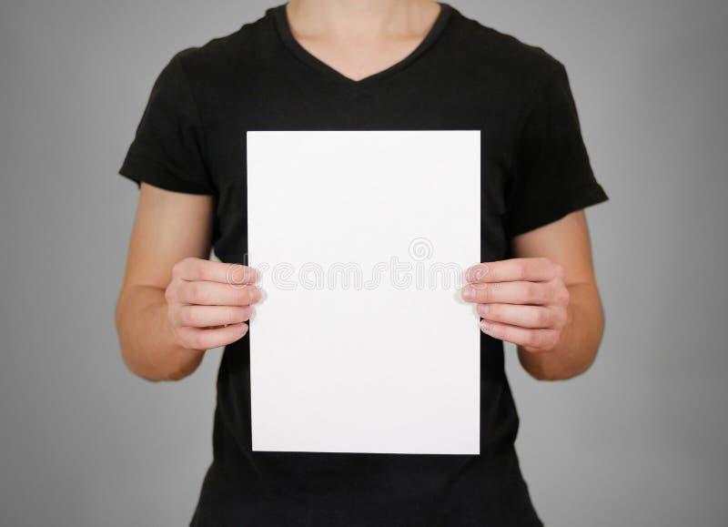 拿着空白的白色A4纸的黑T恤杉的人 prese的传单 免版税库存图片