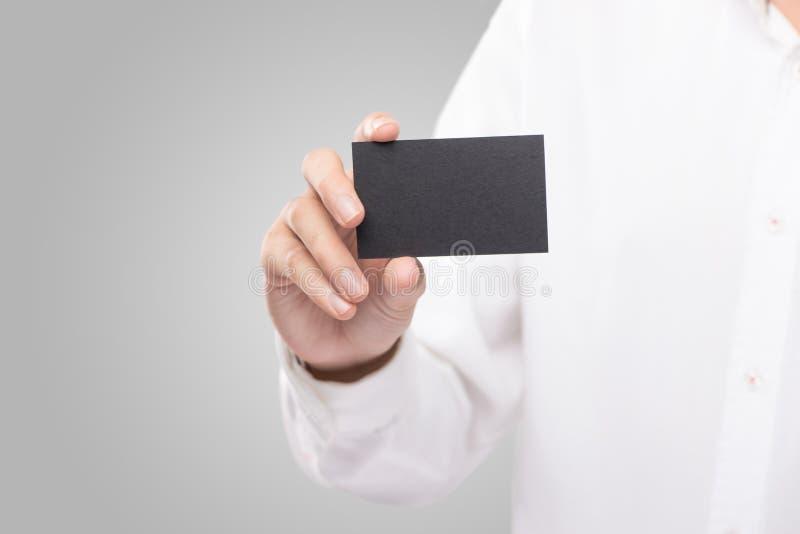 拿着空白的简单的黑名片设计大模型的手 免版税库存照片