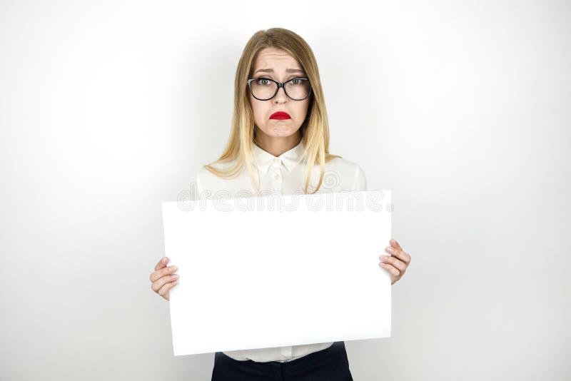 拿着空白的纸片公告被隔绝的白色背景的镜片的年轻美丽的女商人 库存照片