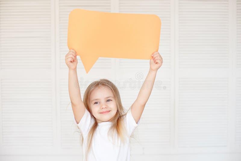 拿着空白的讲话泡影的愉快的矮小的白种人女孩 免版税图库摄影