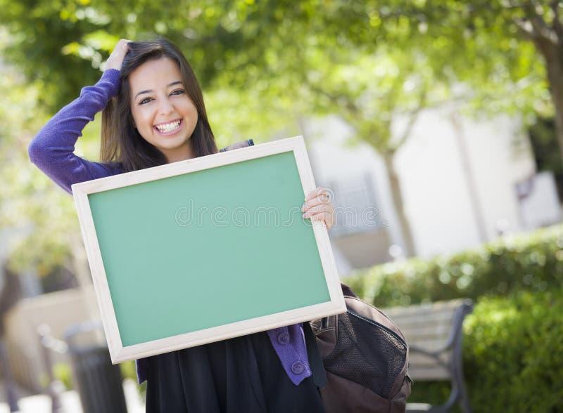 拿着空白的黑板的逗人喜爱的混合的族种女学生 免版税图库摄影