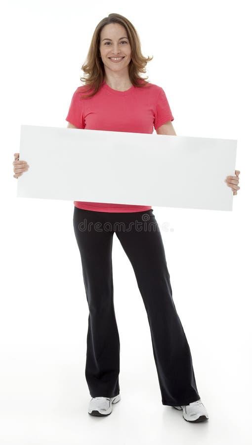 拿着空白符号的可爱的妇女 免版税库存图片