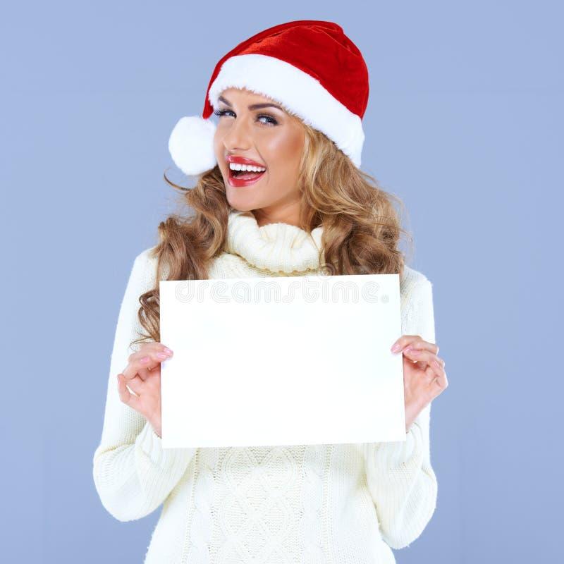 拿着空白董事会的圣诞老人帽子的愉快的妇女 库存图片