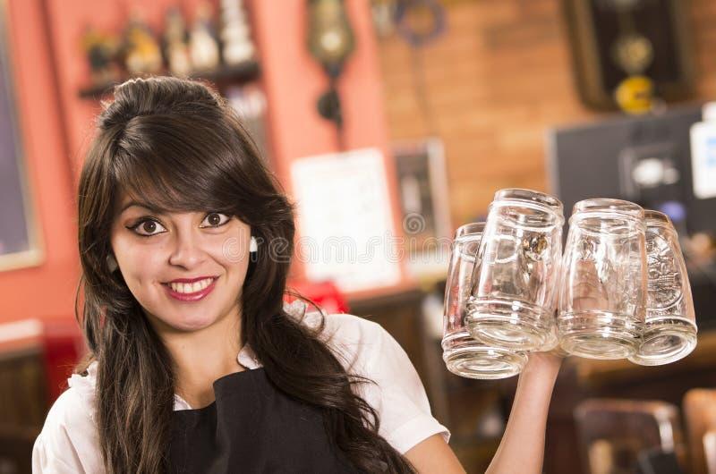 拿着空的啤酒杯的愉快的逗人喜爱的女服务员 免版税库存图片