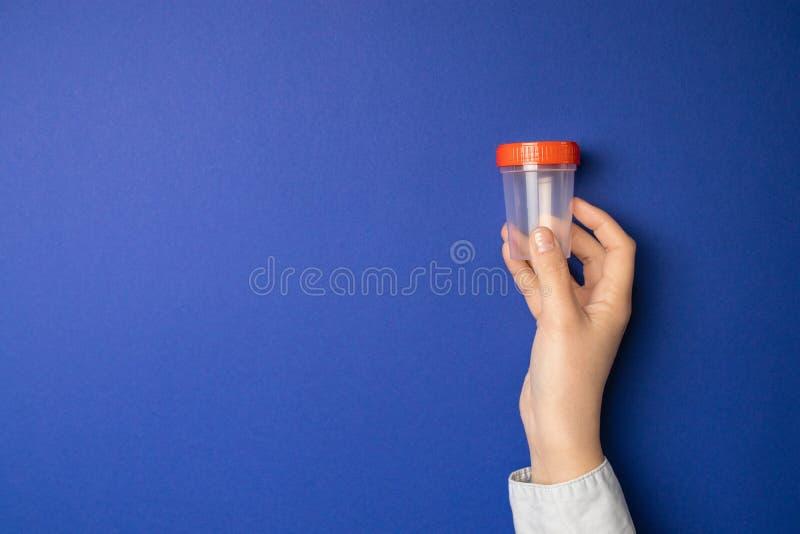 拿着空的塑胶容器的手 免版税库存图片