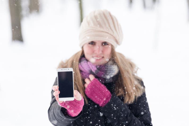 拿着空的屏幕巧妙的电话的美丽的女性在多雪的天 免版税图库摄影