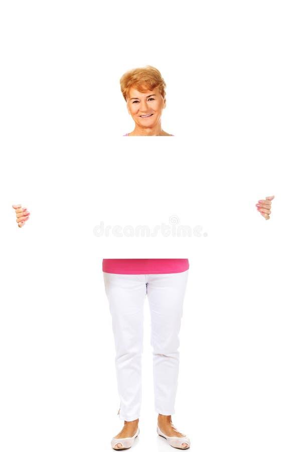 拿着空的横幅的微笑的资深妇女 免版税图库摄影
