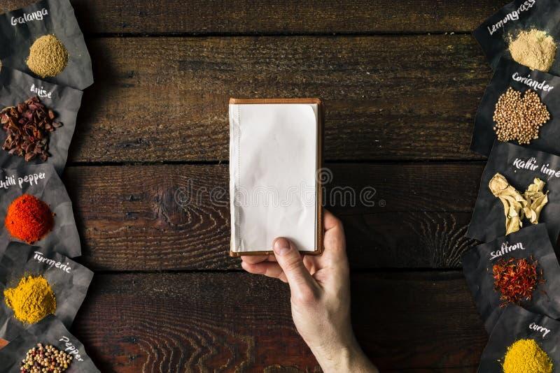 拿着空的笔记本的厨师 烹调概念 平的位置 库存照片