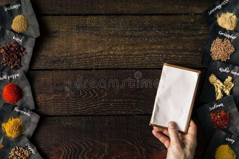 拿着空的笔记本的厨师 烹调概念 平的位置 免版税库存图片