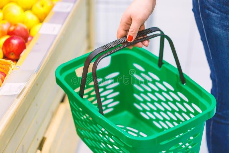 拿着空的绿色手提篮的妇女在果子窗口附近在超级市场 背景袋子概念行程购物的白人妇女 图库摄影