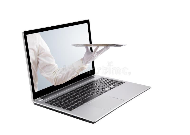 拿着空的银色盘子的侍者在膝上型计算机屏幕外面 免版税库存照片