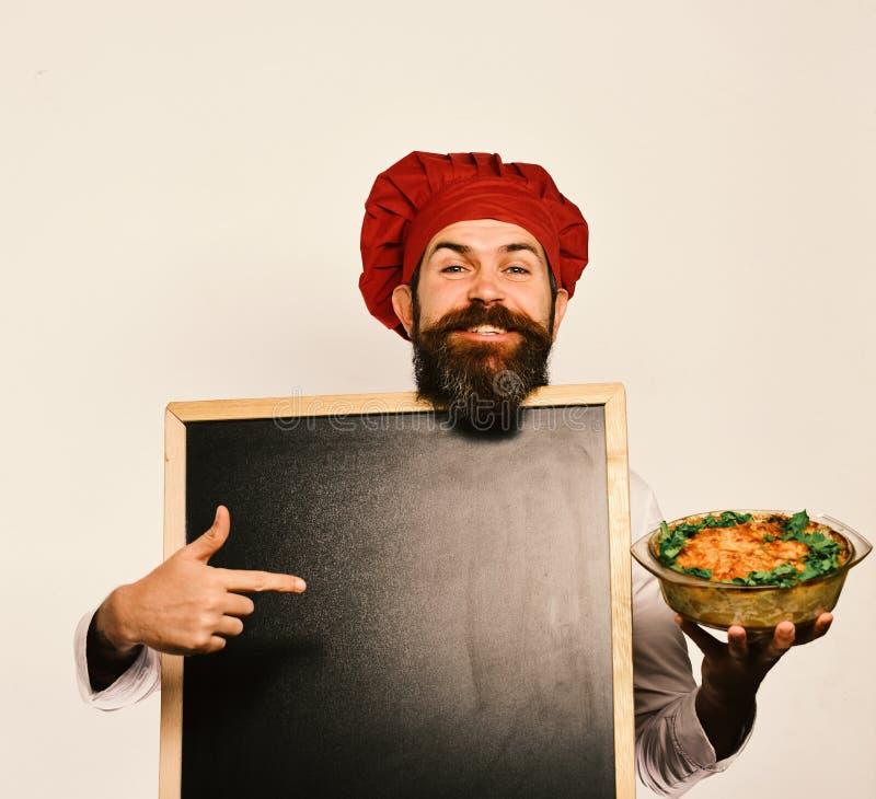 拿着空的黑板和被烘烤的盘的专业厨师 免版税库存照片