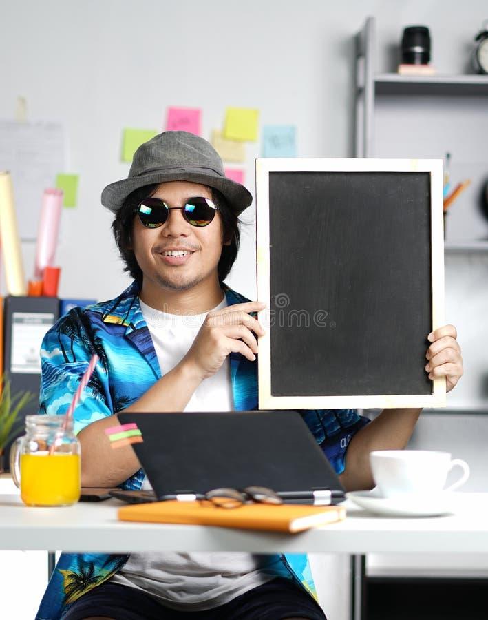 拿着空的黑板的年轻人,当研究夏天Vacat时 库存照片