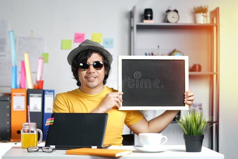 拿着空的黑板的年轻人 免版税库存照片