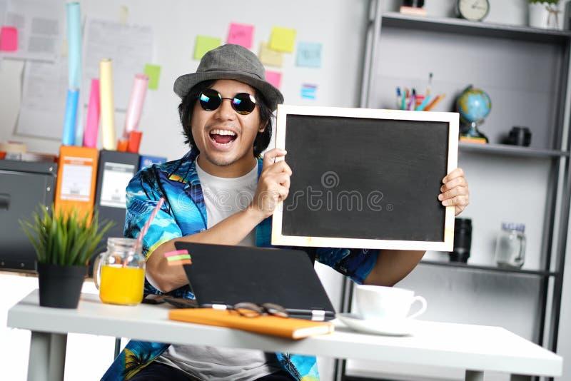 拿着空的黑板的激动的时髦的年轻人,当工作时 库存图片