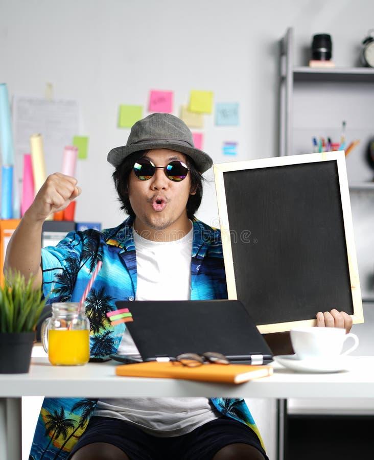 拿着空的黑板的激动的时髦的年轻人,当工作时 免版税库存图片