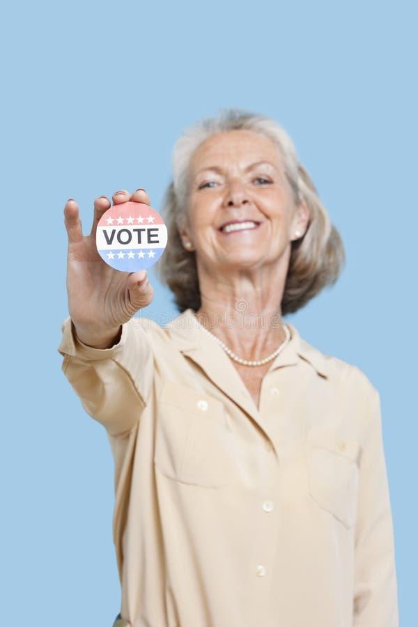 拿着竞选徽章的资深妇女画象反对蓝色背景 免版税库存图片