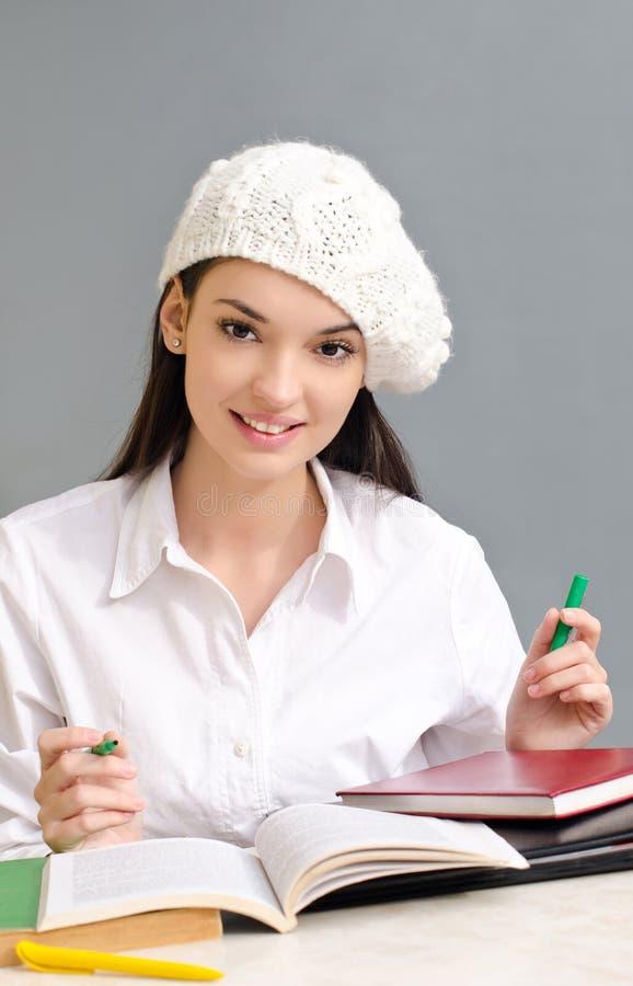 穿着贝雷帽的美丽的学生女孩。 免版税图库摄影