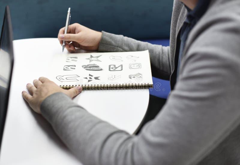 拿着笔记本与的手画了品牌商标创造性的设计想法 库存图片