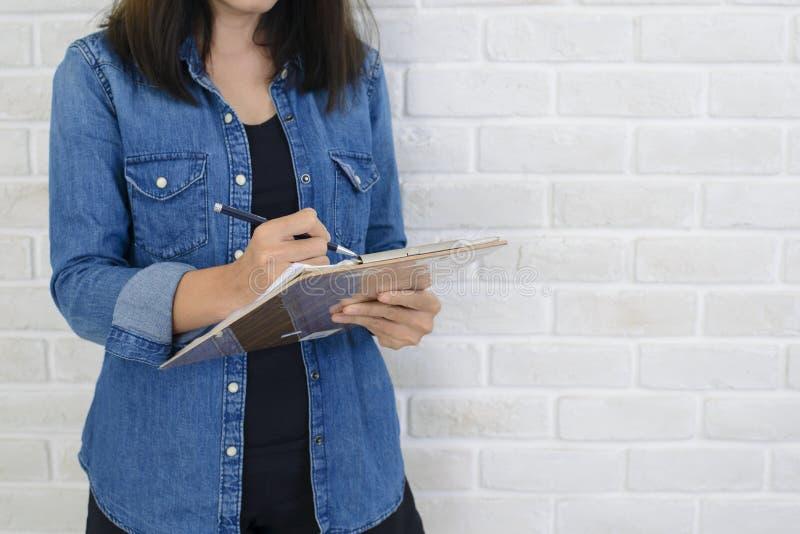 拿着笔记本和笔的妇女手准备好采取站立在白色墙壁附近的笔记 免版税库存图片