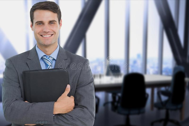 拿着笔记本的商人反对办公室背景 免版税库存照片