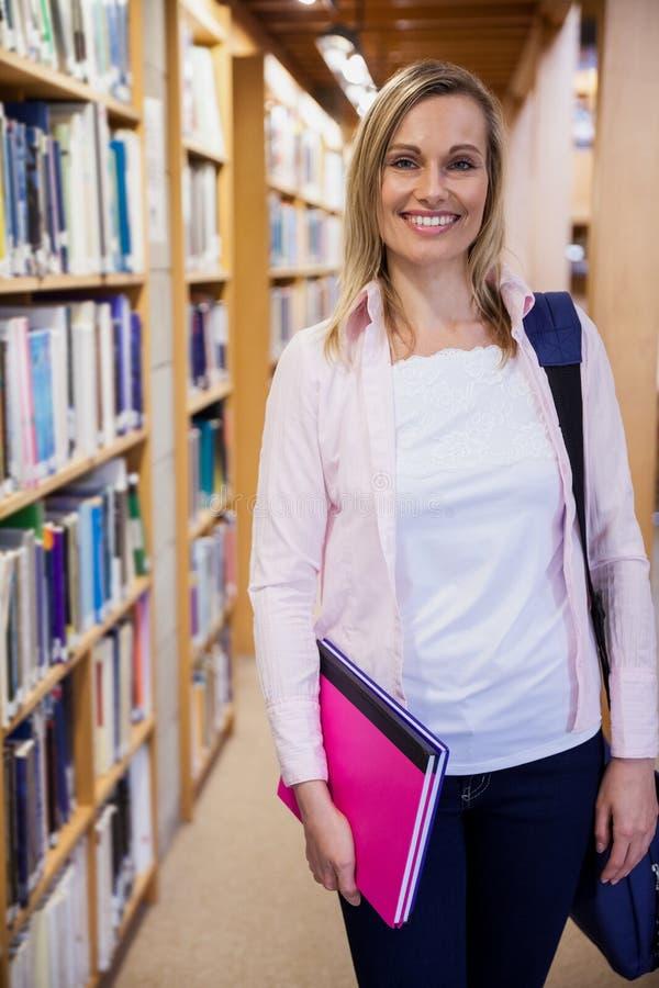 拿着笔记本的女学生在图书馆里 免版税图库摄影