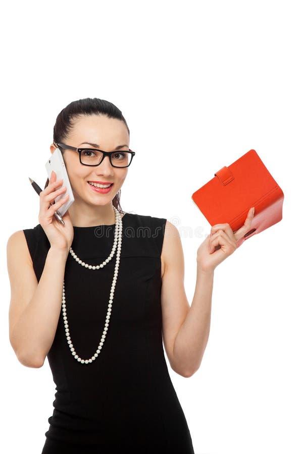 拿着笔记本的女实业家谈话在电话 免版税库存照片