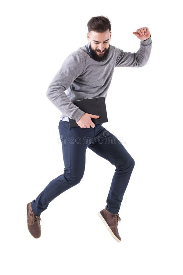 拿着笔记本的愉快的激动的商人跳跃和微笑与握紧拳头 免版税库存照片