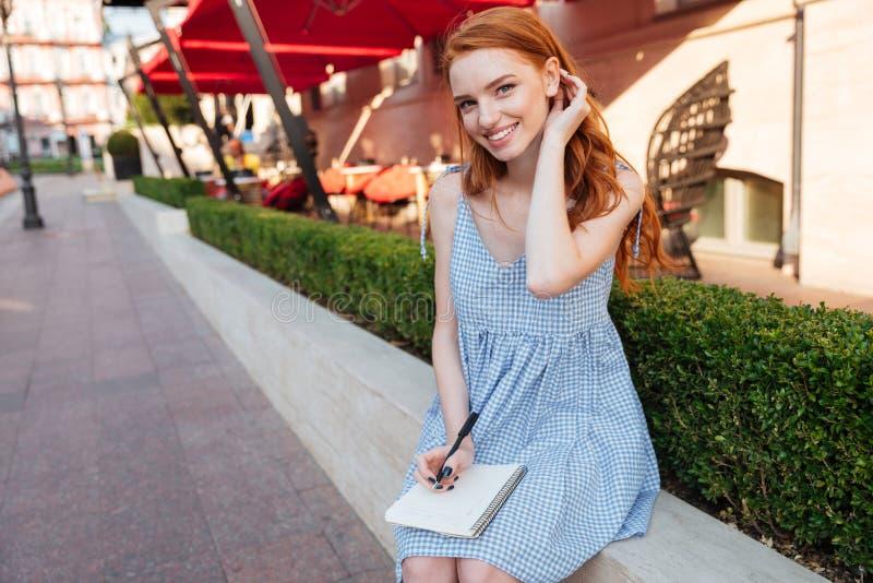 拿着笔记薄和笔的可爱的红头发人女孩 免版税库存图片