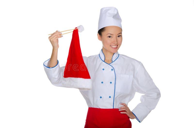 拿着筷子圣诞老人帽子的东部厨师 库存照片