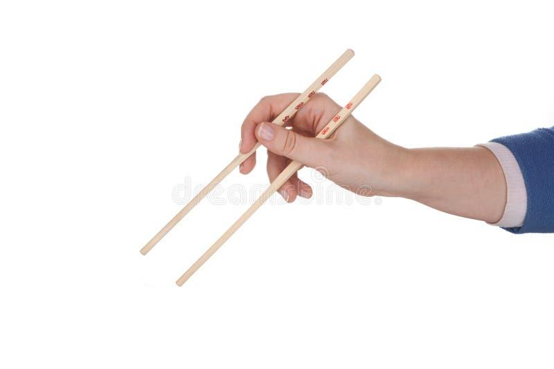 拿着筷子的女性手 免版税库存图片