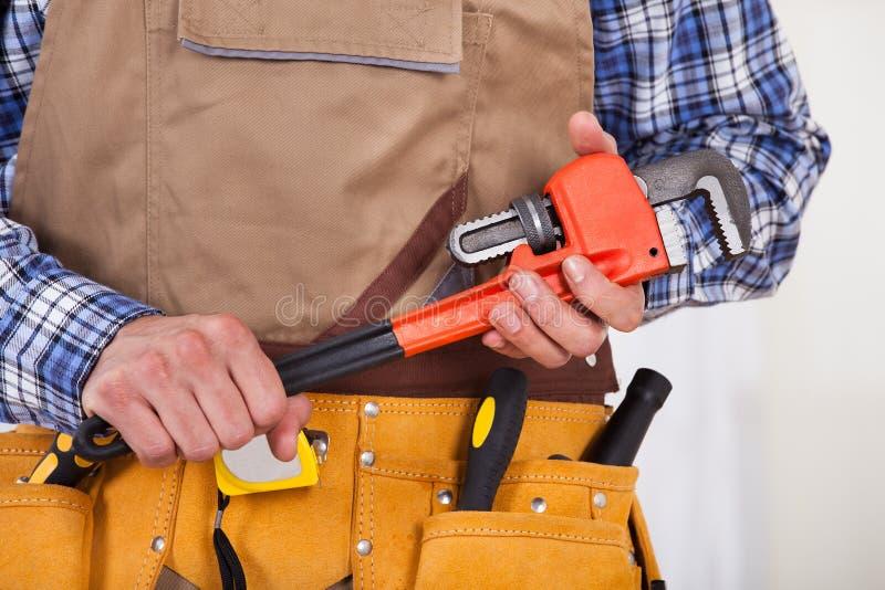 拿着管扳手的安装工 图库摄影