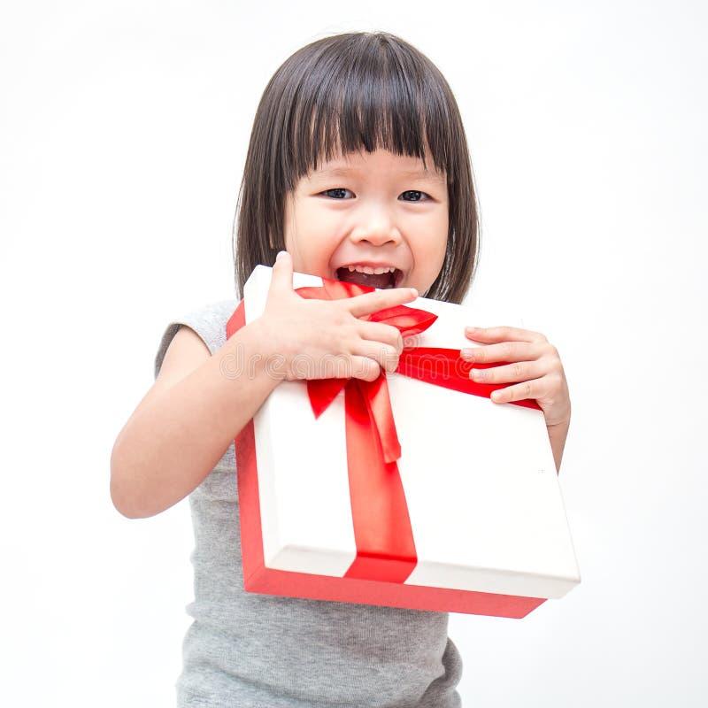 拿着箱子圣诞节礼物的小逗人喜爱的亚裔女孩画象  免版税库存图片
