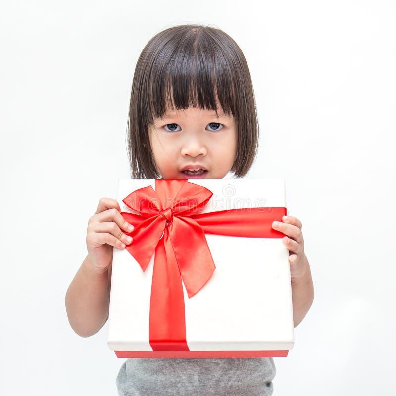 拿着箱子圣诞节礼物的小逗人喜爱的亚裔女孩画象  免版税库存照片