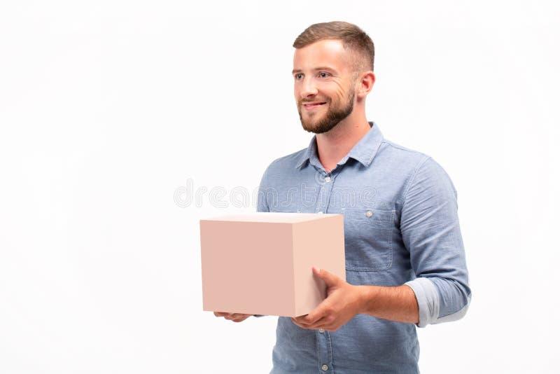 拿着箱子的偶然年轻人被隔绝在白色背景 免版税库存图片
