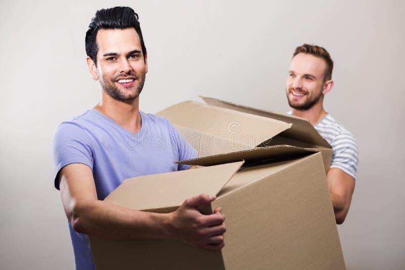 拿着箱子的愉快的快乐夫妇 库存照片